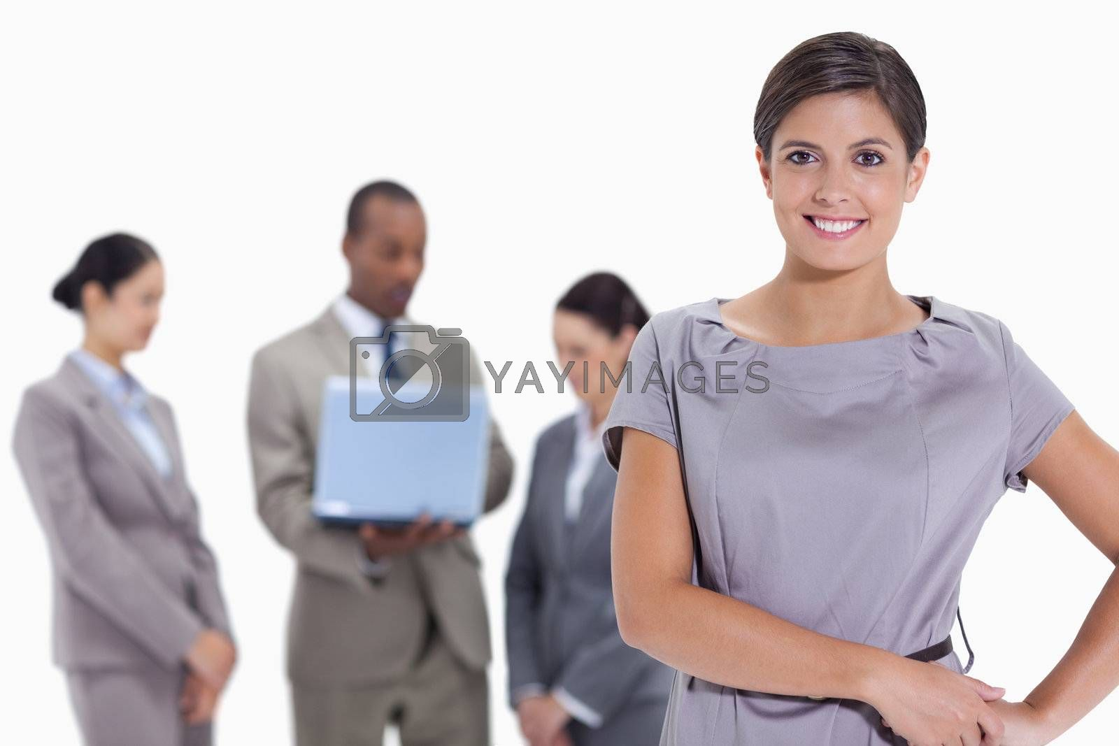 Woman with hands on her hips with business team in the background against white background