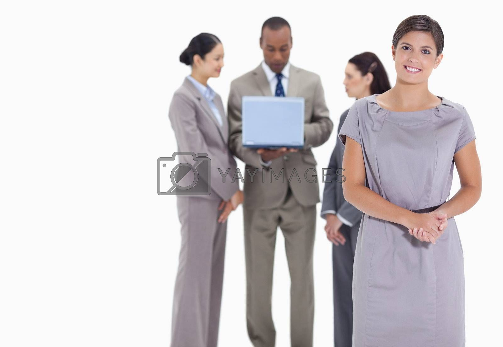 Woman welcoming and holding her hands and co-workers talking with a laptop in the background