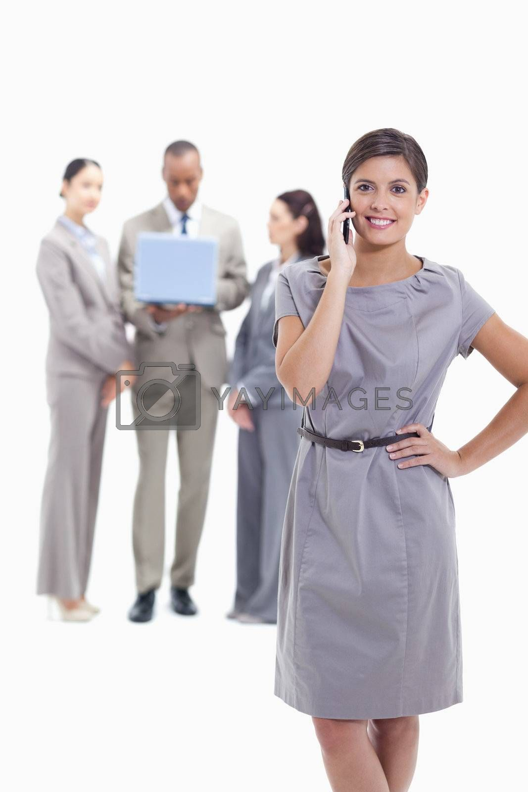 Businesswoman on the phone with a hand on her hip and crossing her legs, with co-workers in the background with a laptop