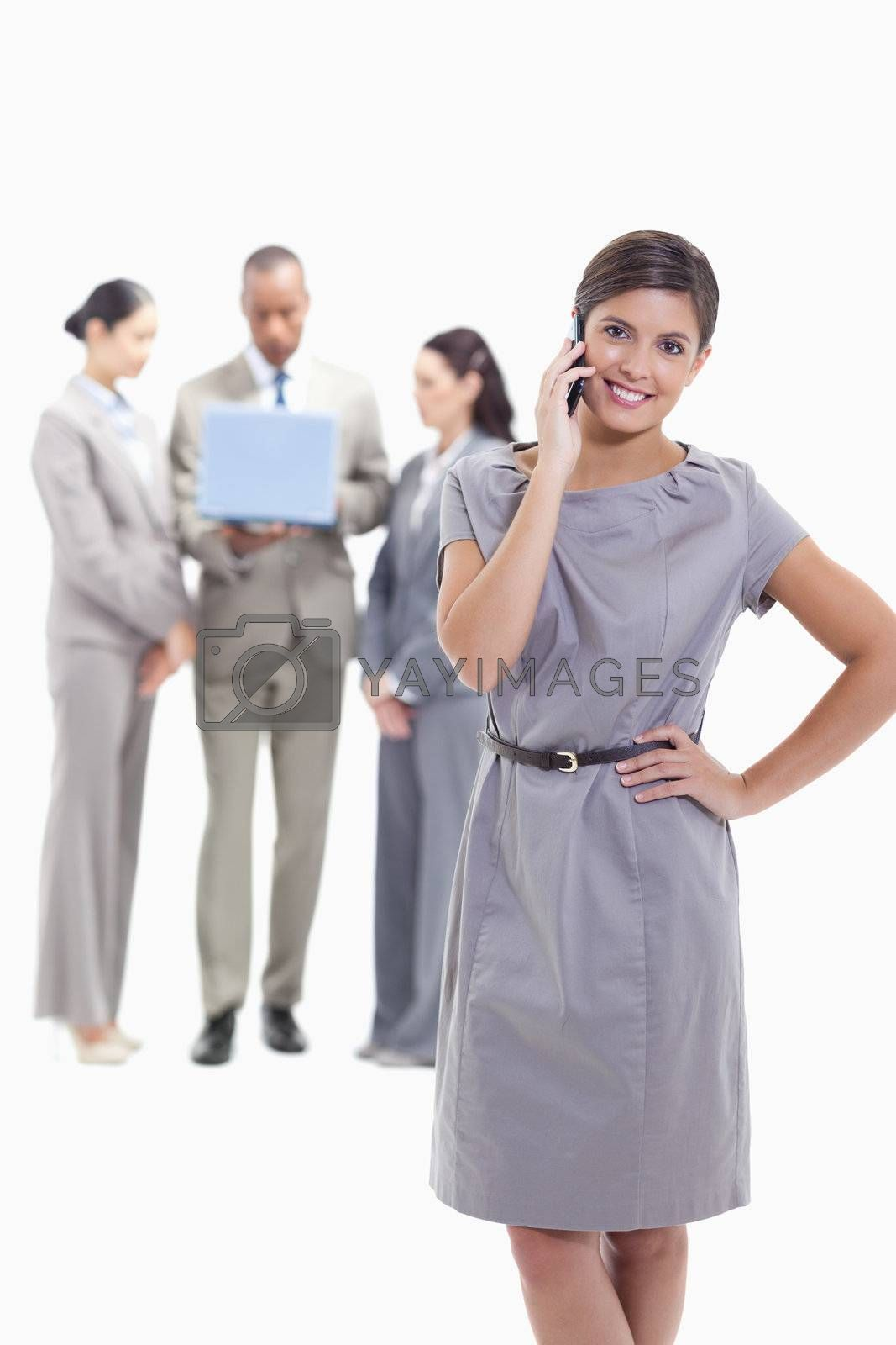 Businesswoman on the phone with a hand on her hip, her legs crossing and her head tilted with co-workers in the background watching a laptop screen