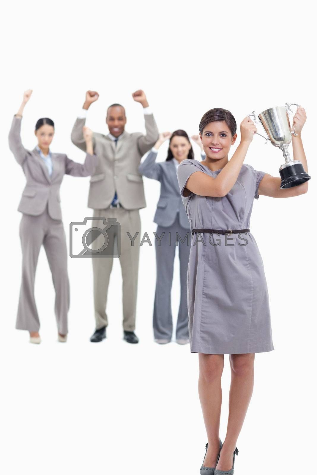 Picture centered on co-workers raising their arms in the background with a woman smiling and holding up a cup