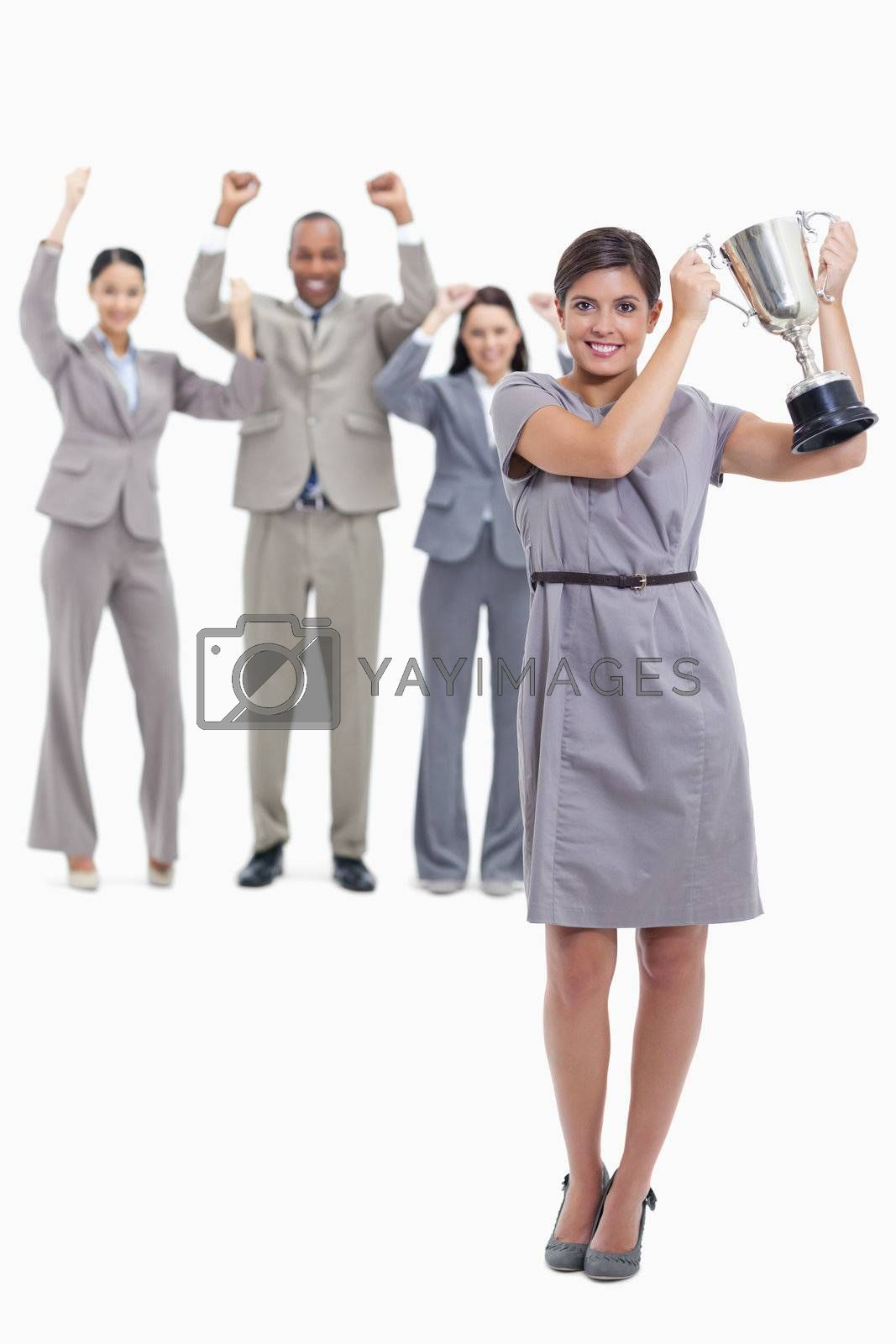 Picture centered on woman smiling and holding up a cup with co-workers raising their arms in the background