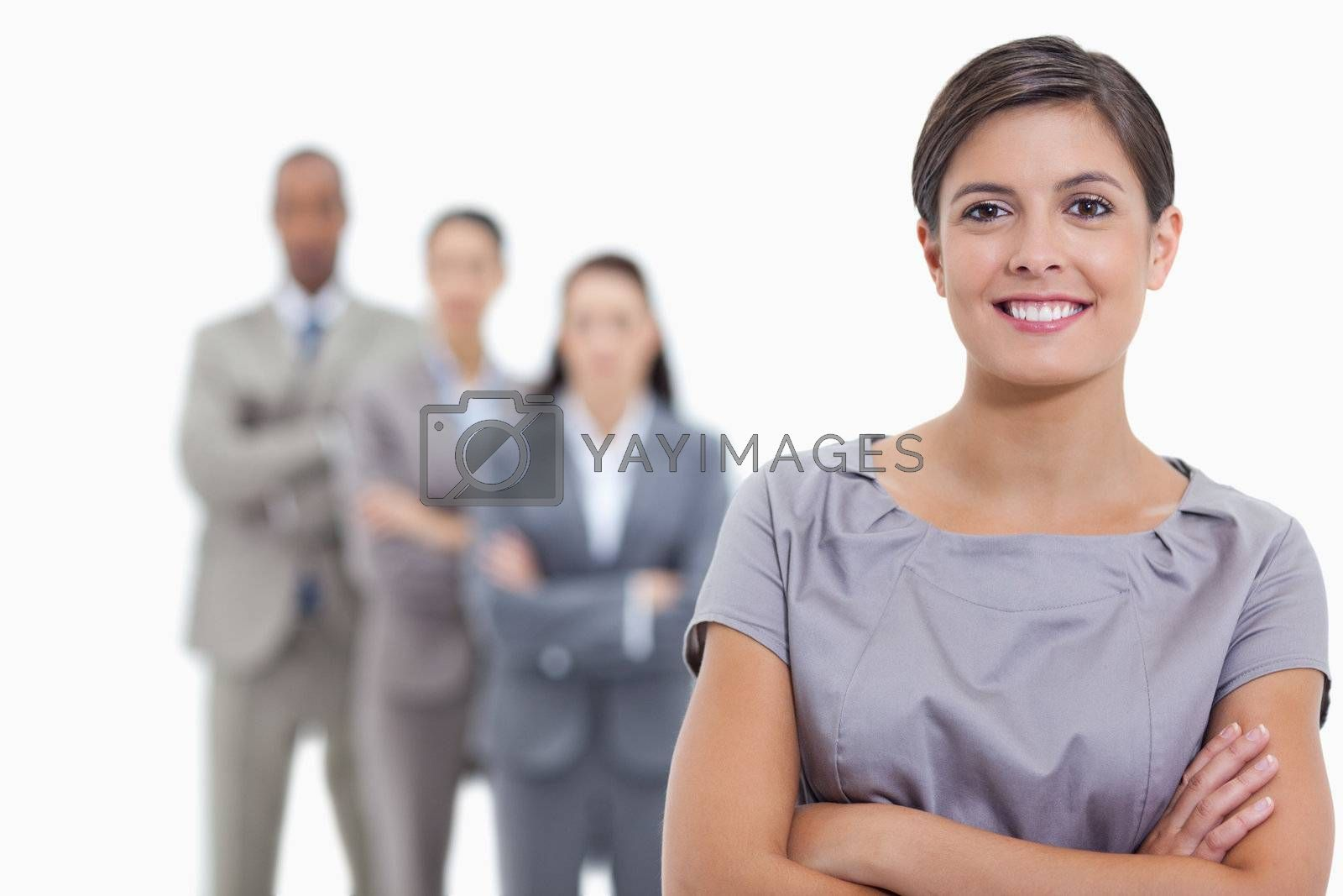 Close-up of a business team crossing their arms and standing behind each other with focus on the foreground woman who is smiling