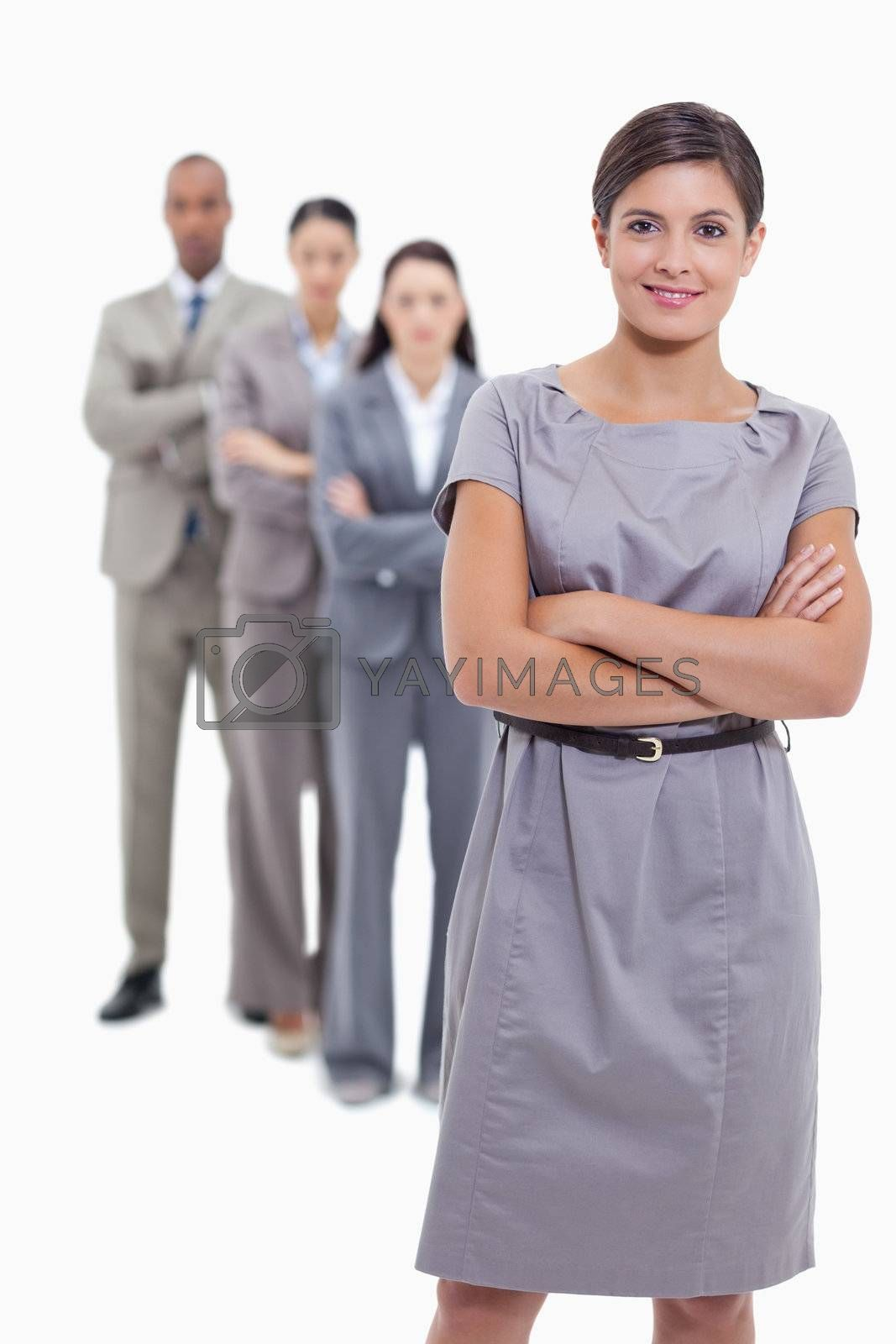 Business team crossing their arms and standing behind each other with focus on the foreground woman who is smiling