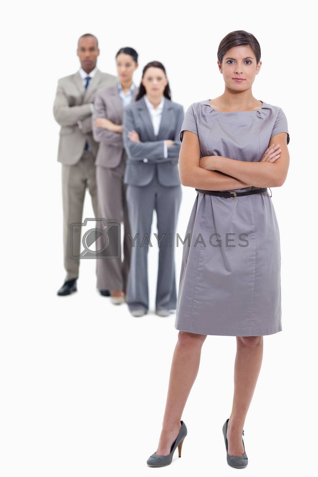 Businesswoman with a discrete smile and a team crossing their arms and standing behind each other against white background
