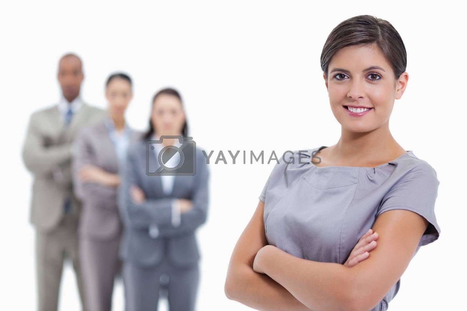 Close-up of a businesswoman smiling and a team crossing their arms against white background