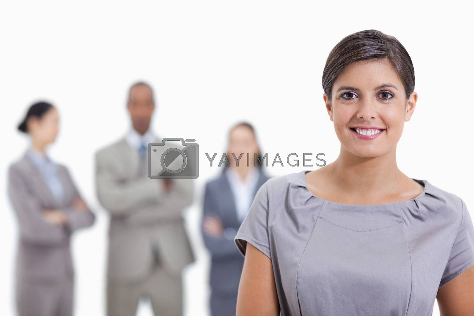 Close-up of a businesswoman smiling and a team crossing their arms in background