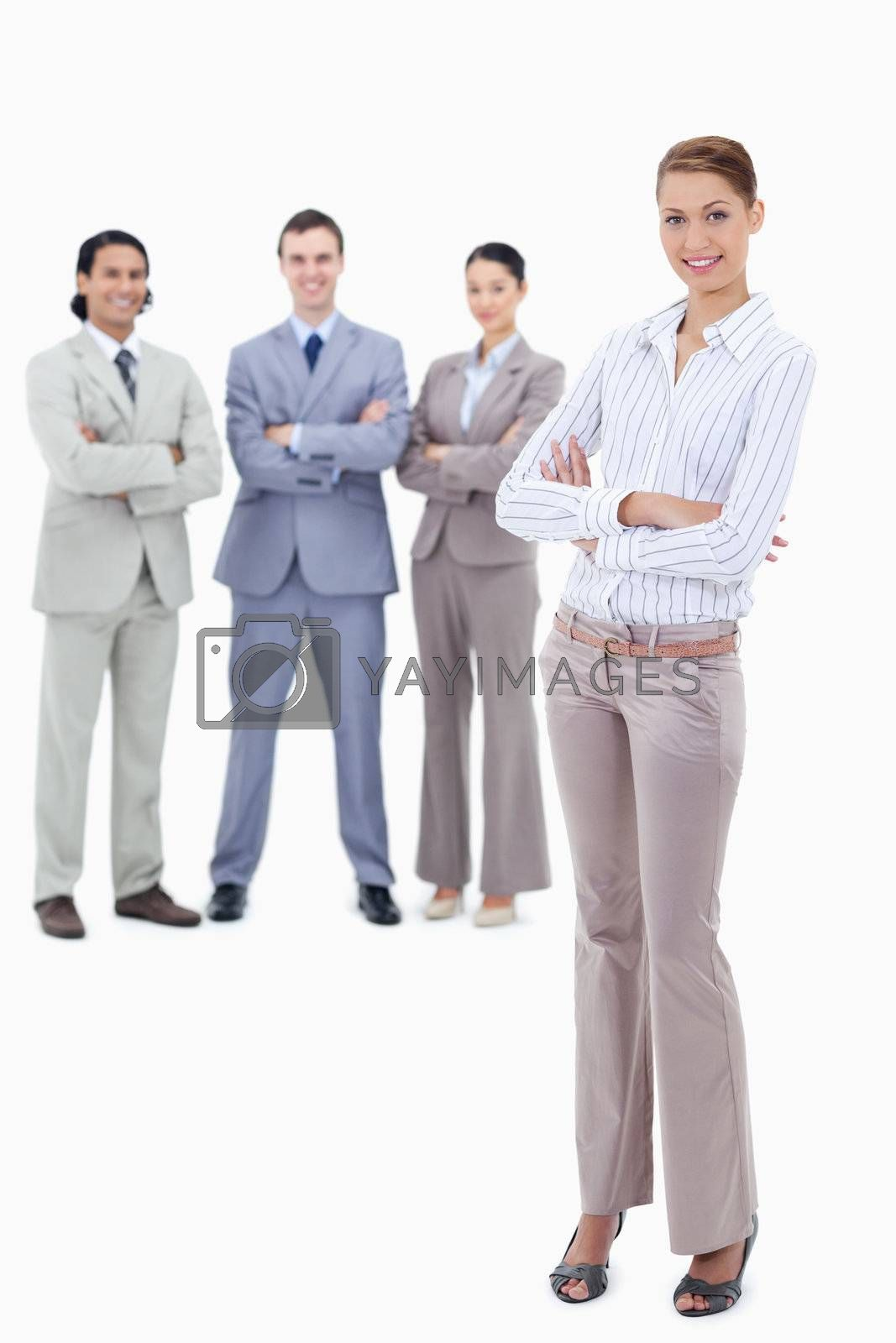 Secretary smiling and crossing her arms with happy business people behind her against white background