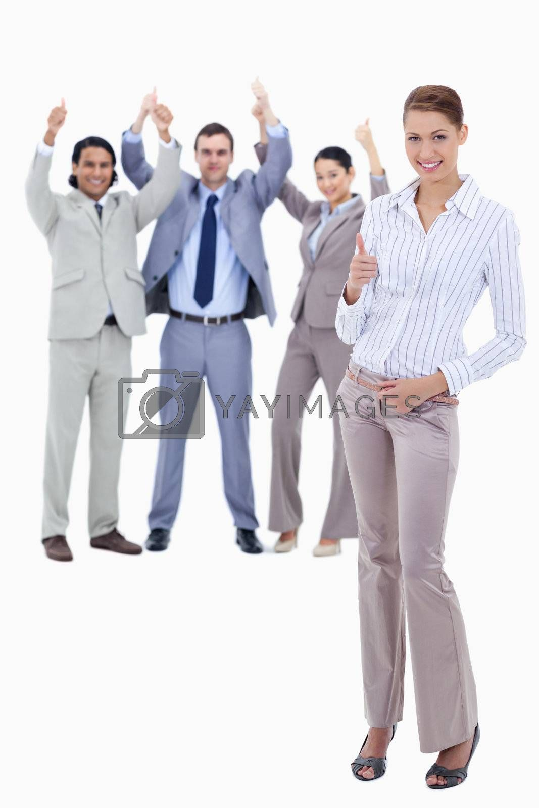 Secretary in foreground and business people with their thumbs up against white background