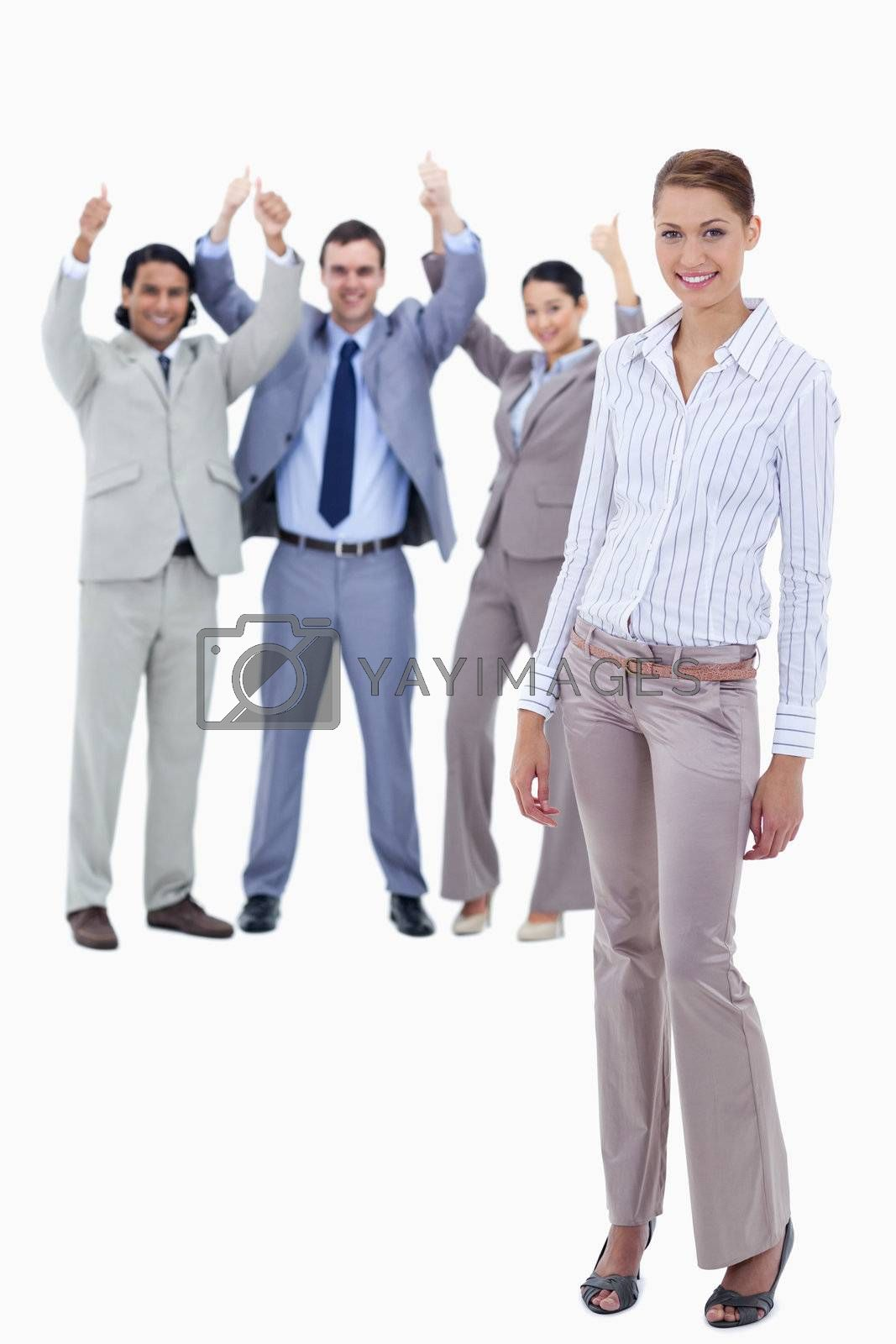 Secretary smiling with her arms along her body and business people with the thumbs up in the background