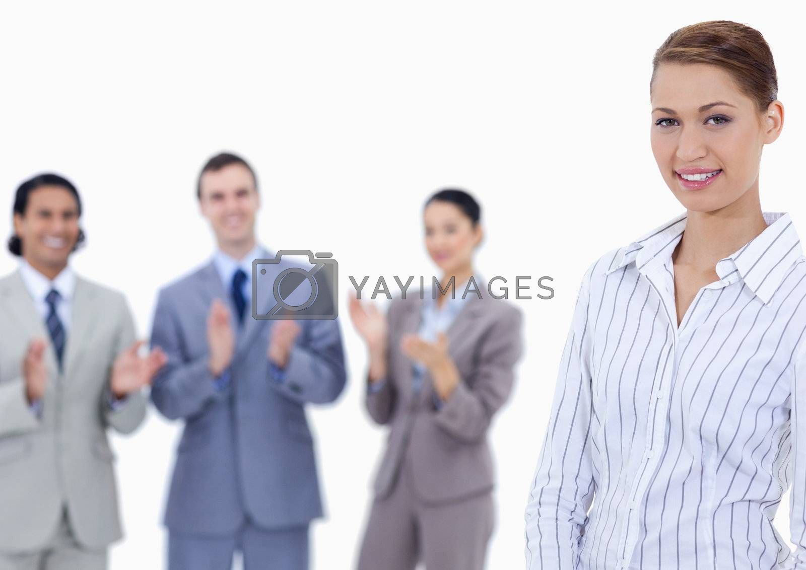 Close-up of a woman smiling with business people applauding while watching her against white background