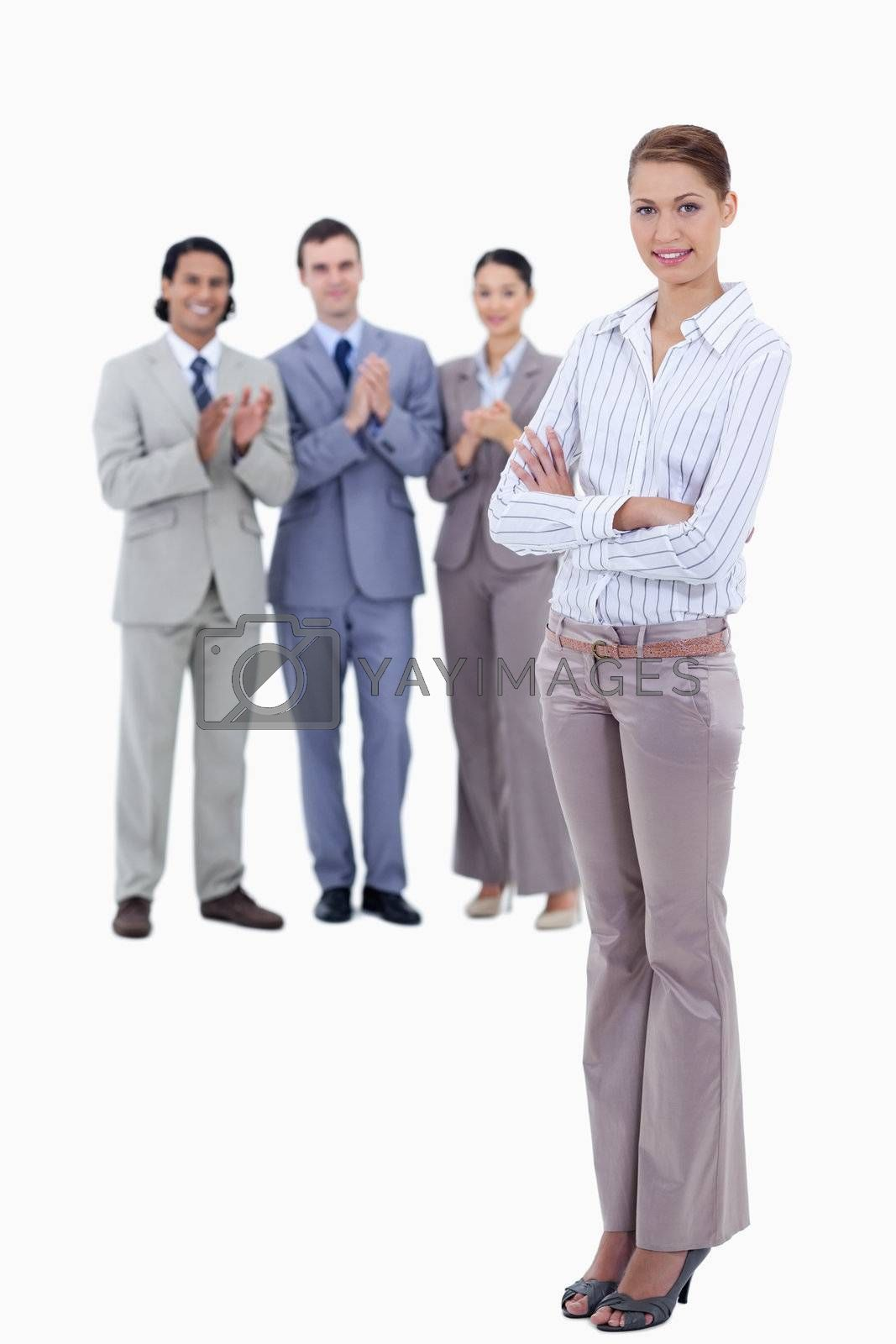 Woman crossing her arms with business people applauding while watching her against white background