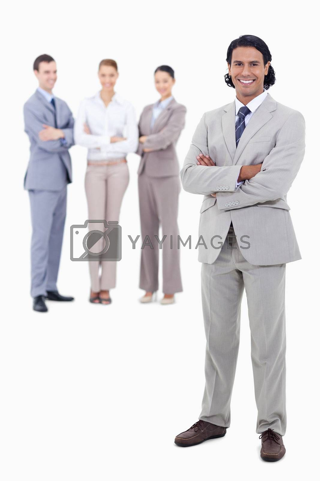 Businessman smiling and crossing his arms with happy people behind him against white background