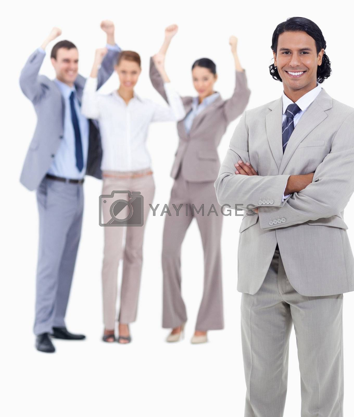 Small close-up of a businessman smiling and crossing his arms with enthusiastic people behind him against white background