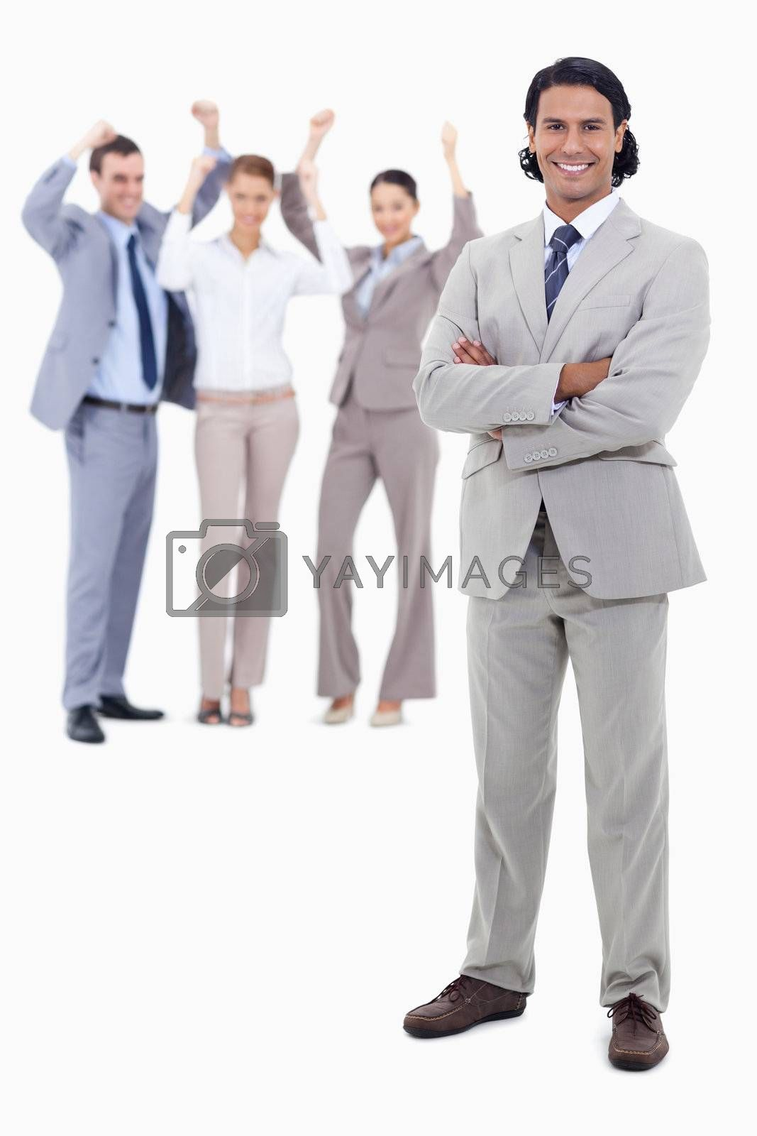 Businessman smiling and crossing his arms with cheering people behind him against white background