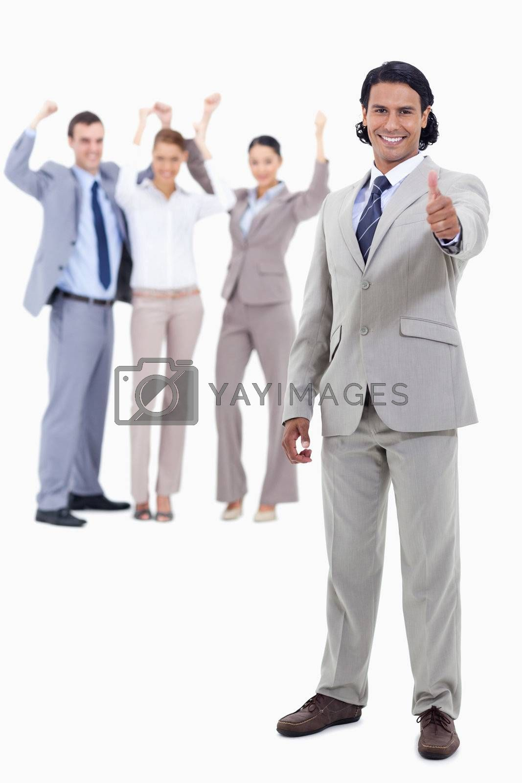 Businessman smiling with his thumbs up and cheering people behind him against white background