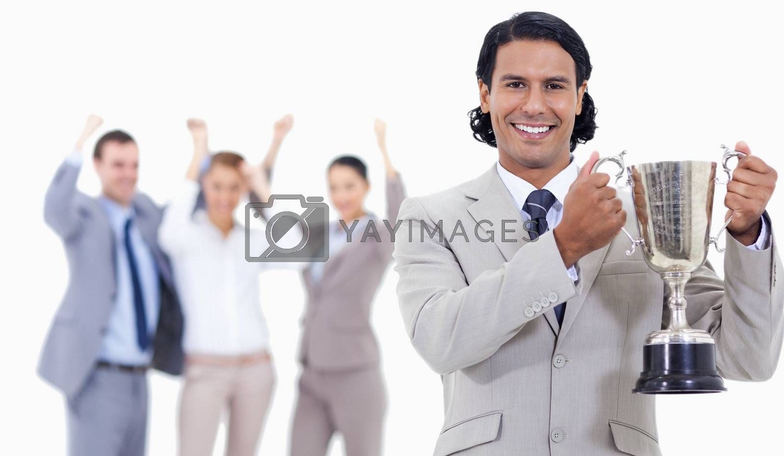 Close-up of a businessman smiling and holding a cup with people cheering behind him against white background