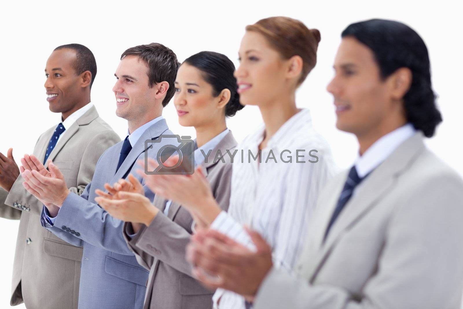 Close-up of people dressed in suits smiling and applauding with focus on the first three people against white background