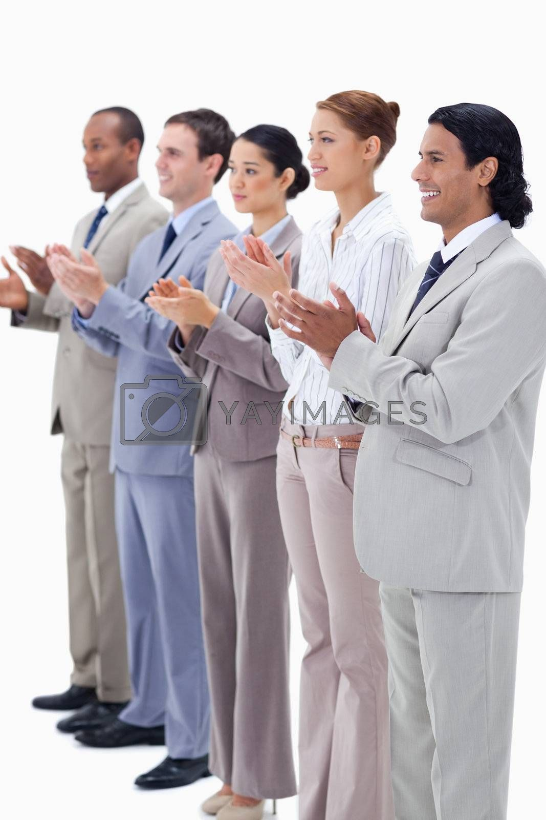 People dressed in suits smiling and applauding while looking towards the left side against white background