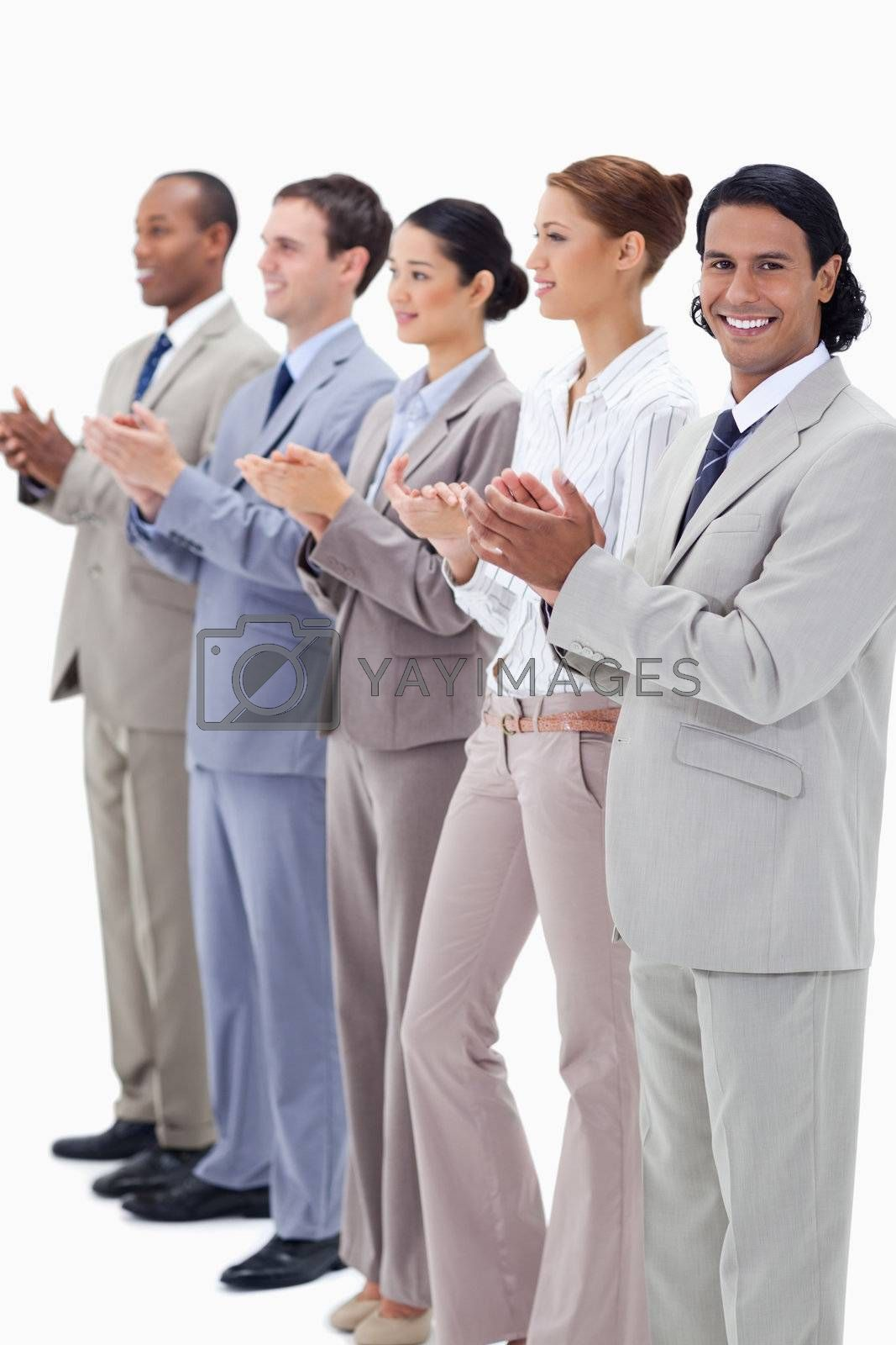 Business team smiling and applauding while looking towards the left side except for one against white background