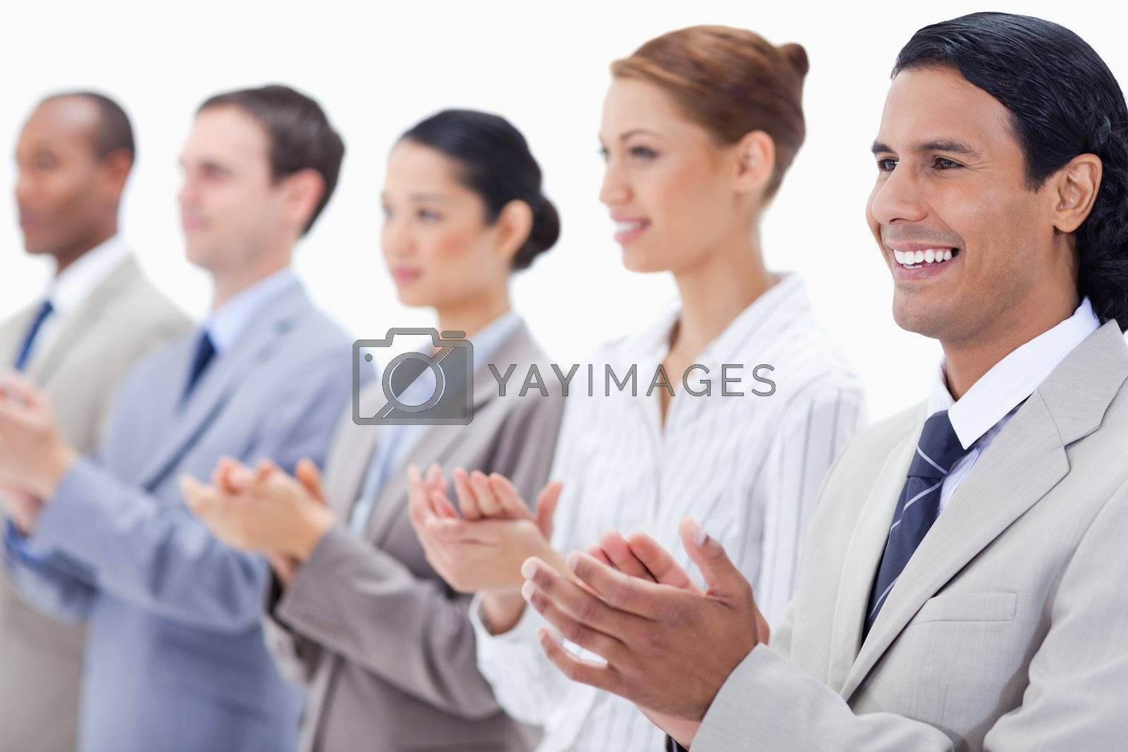 Business team applauding while looking towards the left side with focus on the first man against white background