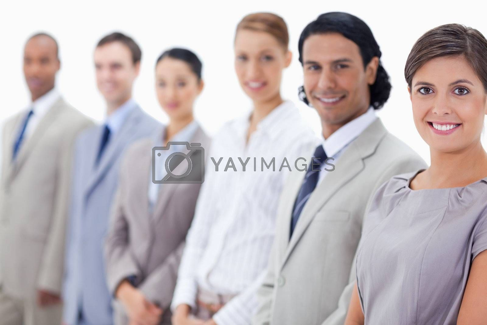 Close-up of a smiling business team looking straight with focus on the first woman