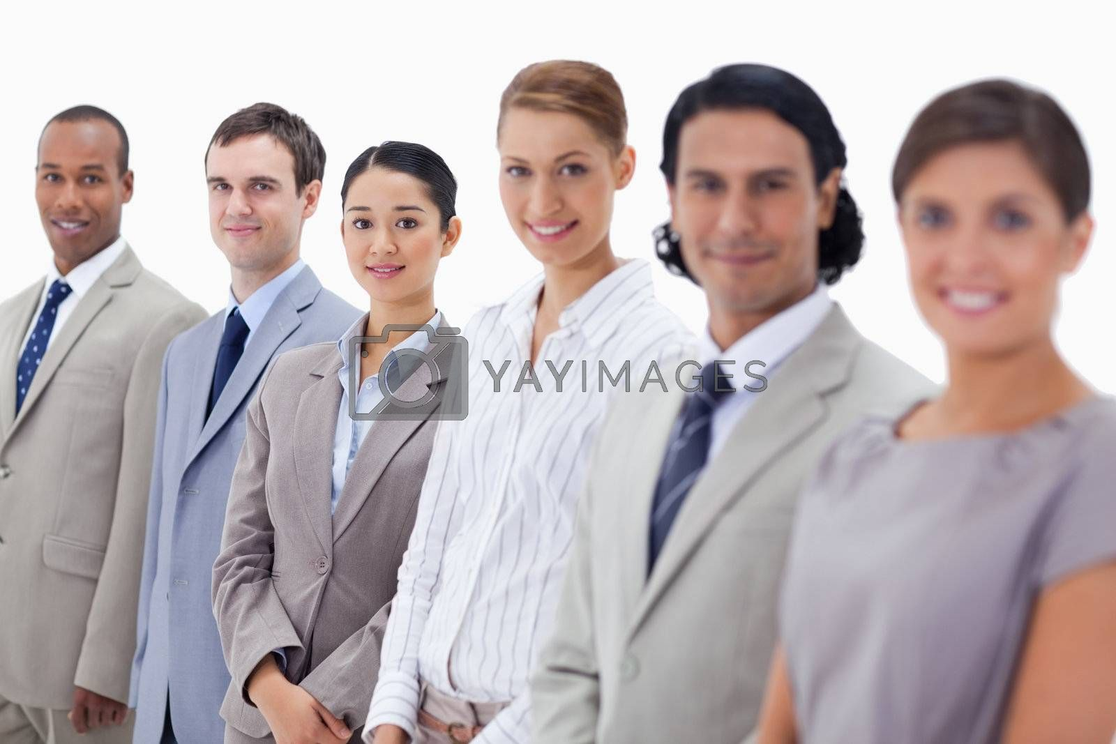 Close-up of smiling people dressed in suits looking straight with focus on the last three people