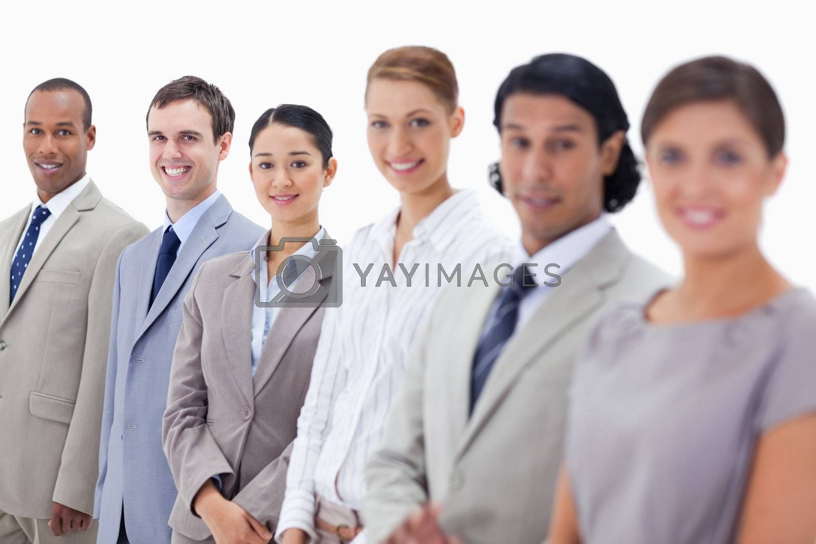 Close-up of business people smiling and looking straight with focus on the last three people