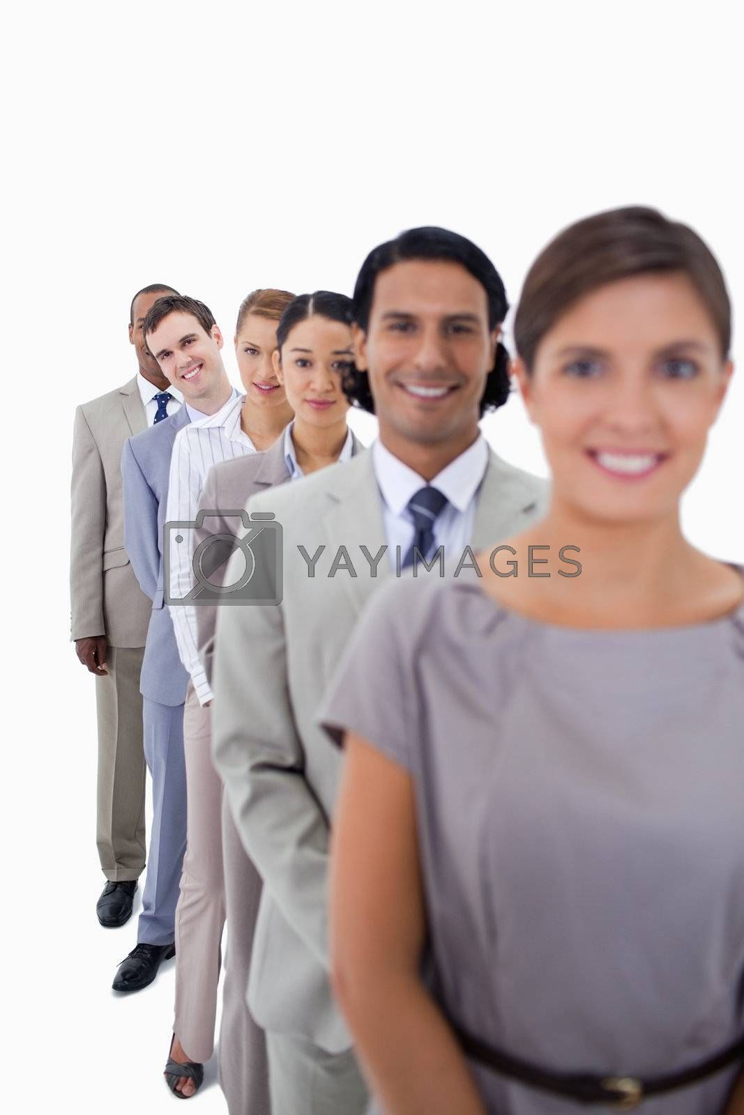 Close-up of workmates in single line smiling and looking straight with focus on the second man against white background