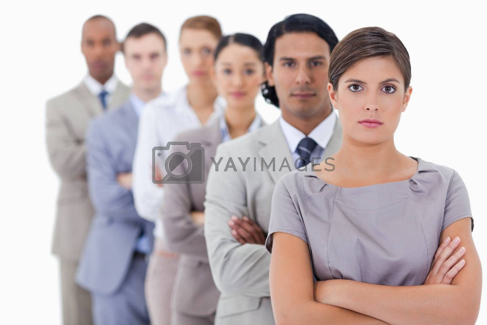 Big close-up of serious workmates in single a line crossing their arms with focus on the first woman