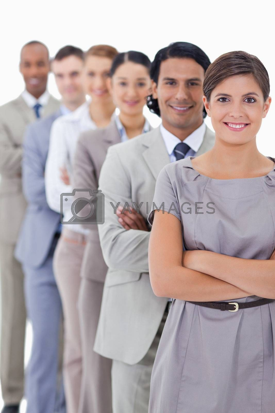 Close-up of workmates smiling in a single line crossing their arms with focus on the first woman