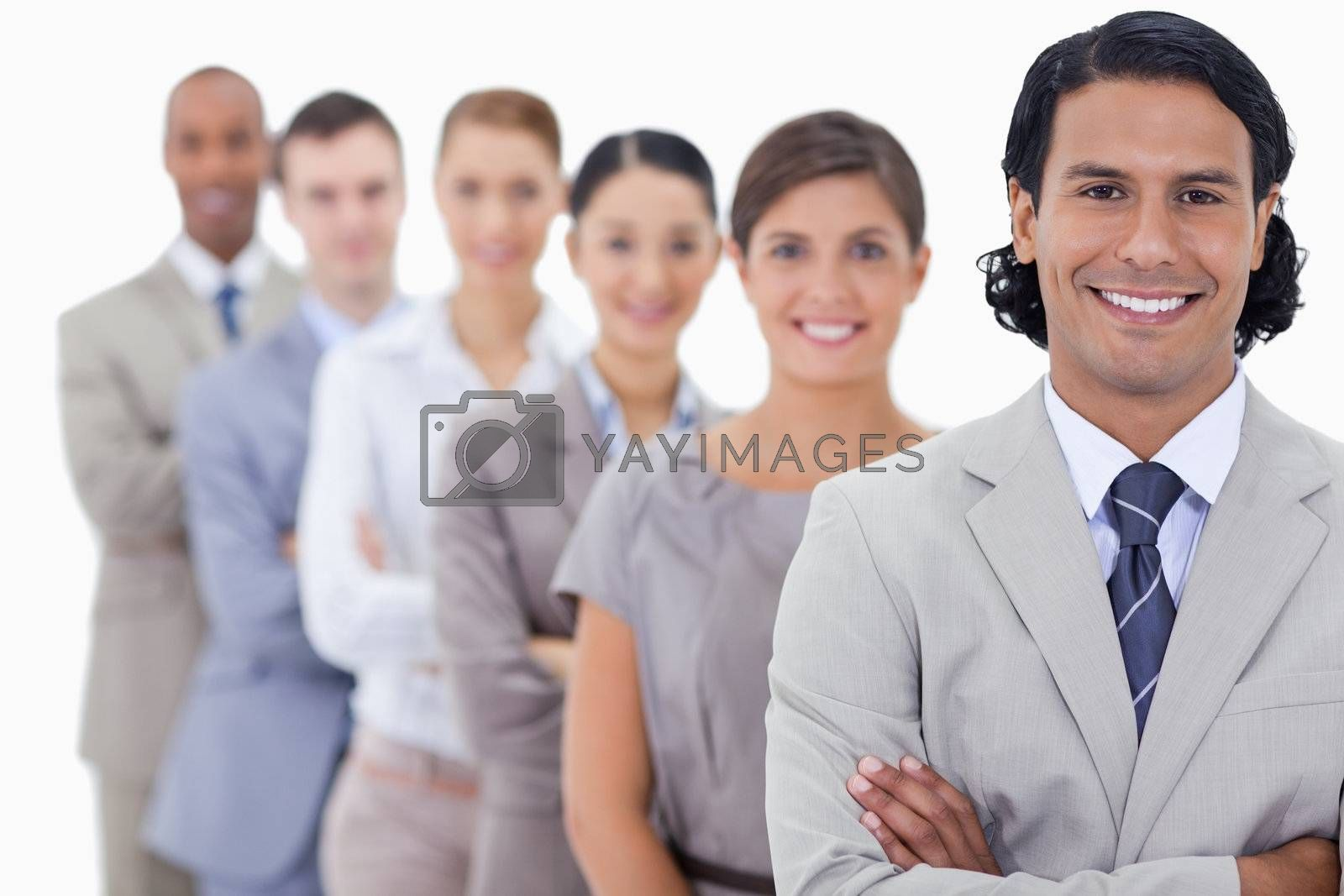 Big close-up of happy workmates in a single line with focus on the first man with his arms crossed.