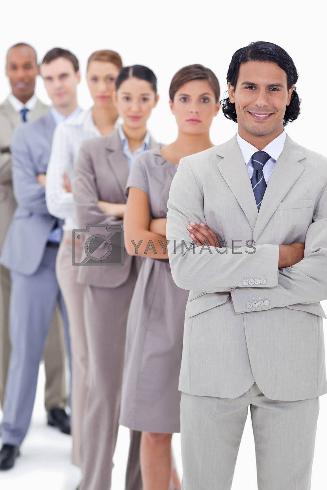 Close-up of a business team crossing their arms in a single line with focus on the first man smiling