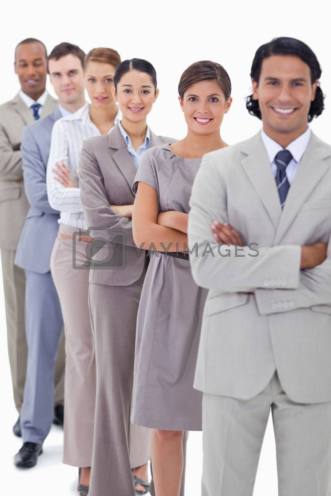 Close-up of a business team in a single line crossing their arms with focus on the first woman