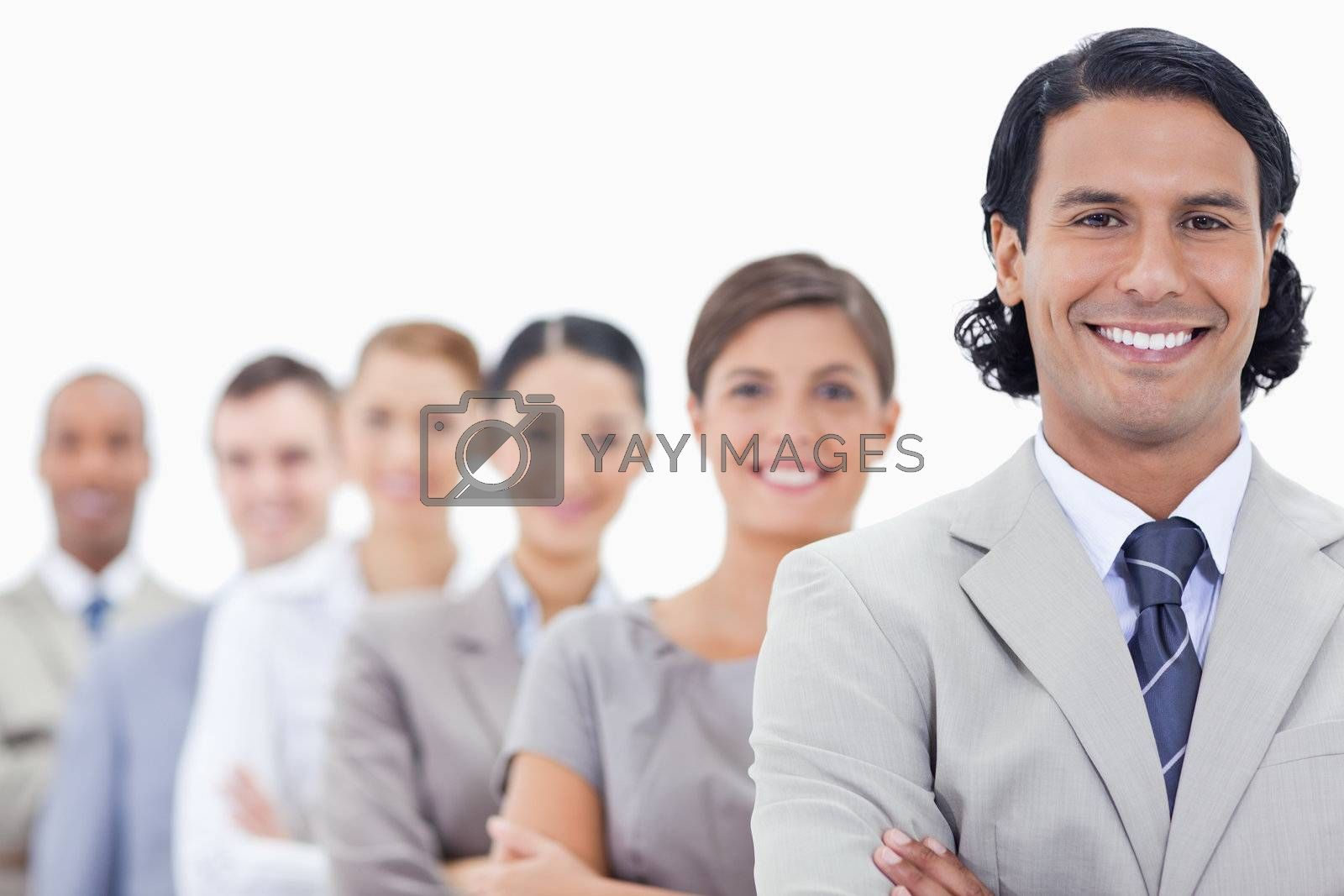 Big close-up of a happy business team crossing their arms in a single line looking straight with focus on the first man