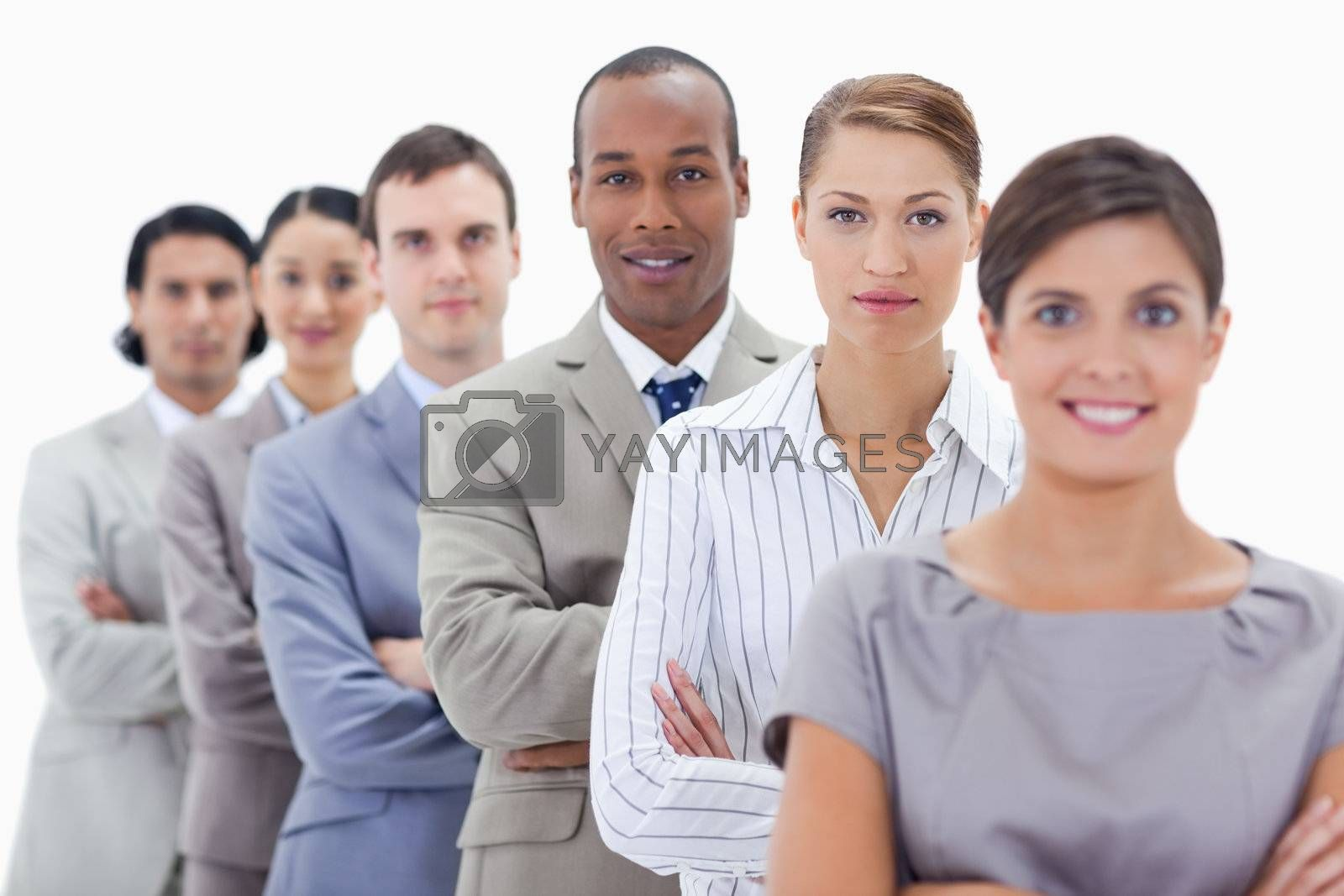 Big close-up of a business team in a single line crossing their arms with focus on the first man