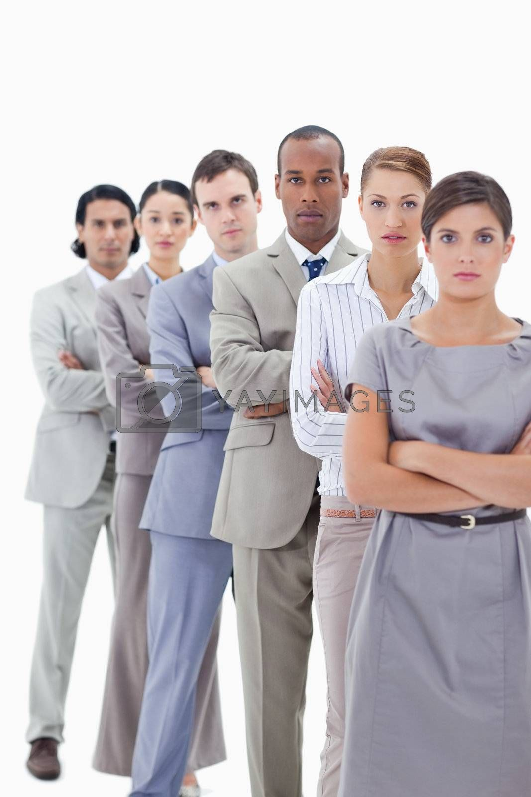 Close-up of a serious business team crossing their arms in a single line against white background