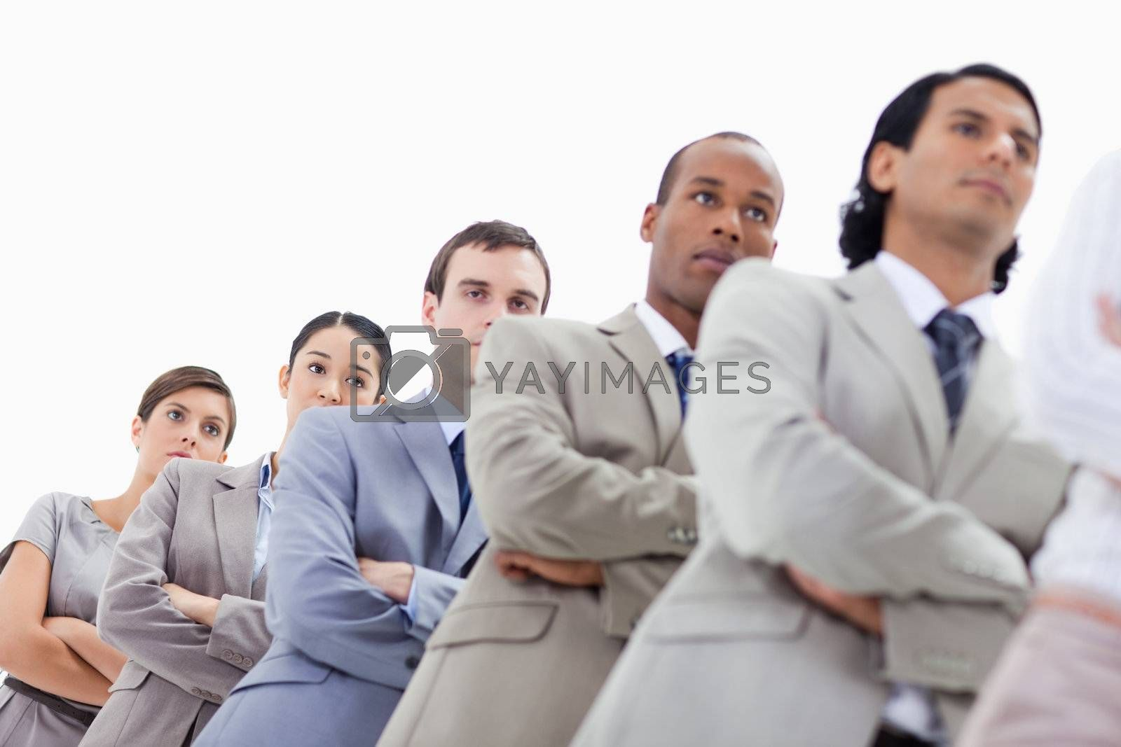 Low-angle shot of people dressed in suits crossing their arms in a single line with focus on the last two women