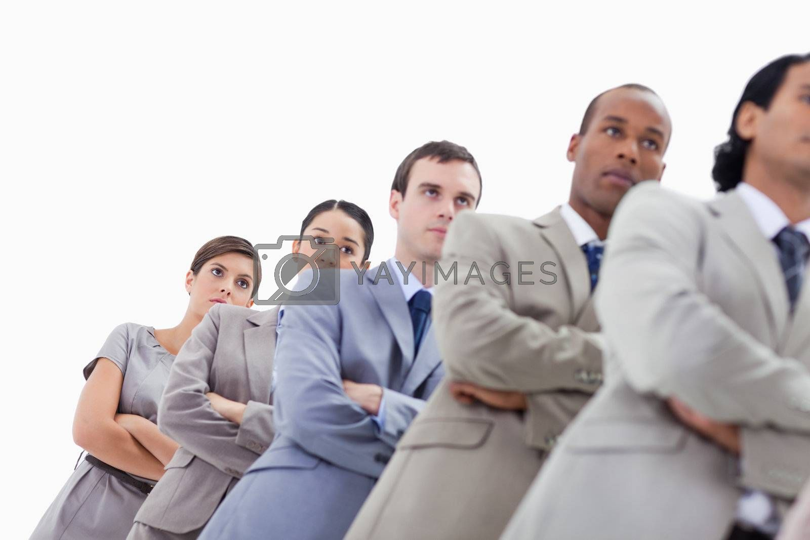 Low-angle shot of colleagues crossing their arms in a single line with focus on the last two women