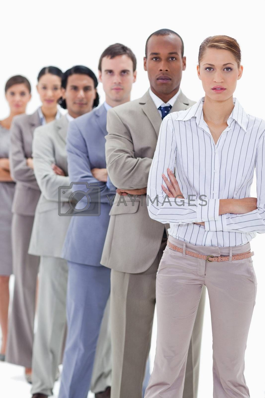 Serious colleagues dressed in suits crossing their arms in a single line with focus on the two first people