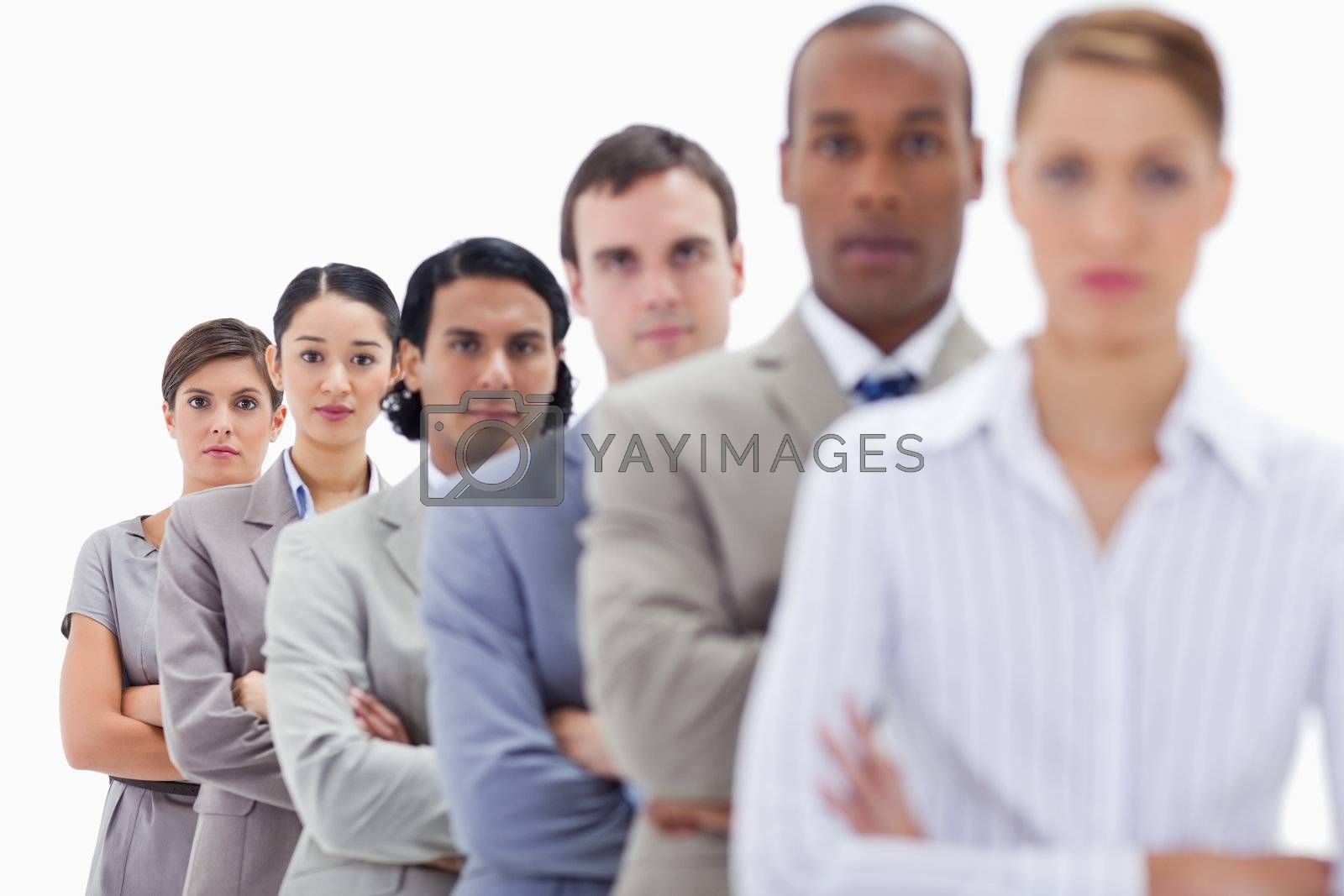 Close-up of serious workmates dressed in suits crossing their arms in a single line with focus on the last two women