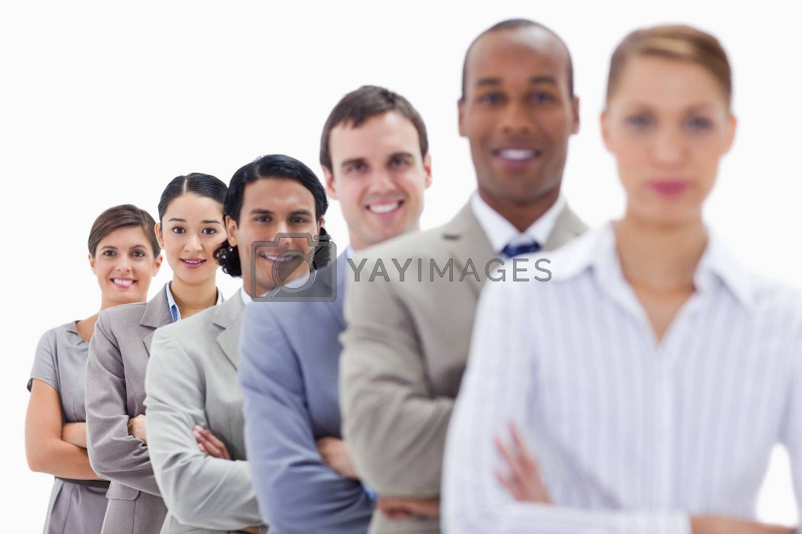 Close-up of happy workmates dressed in suits crossing their arms in a single line with focus on the last two people