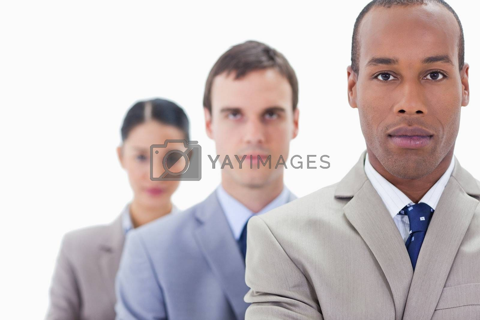 Big close-up of a business team in a single line looking straight with focus on the first man