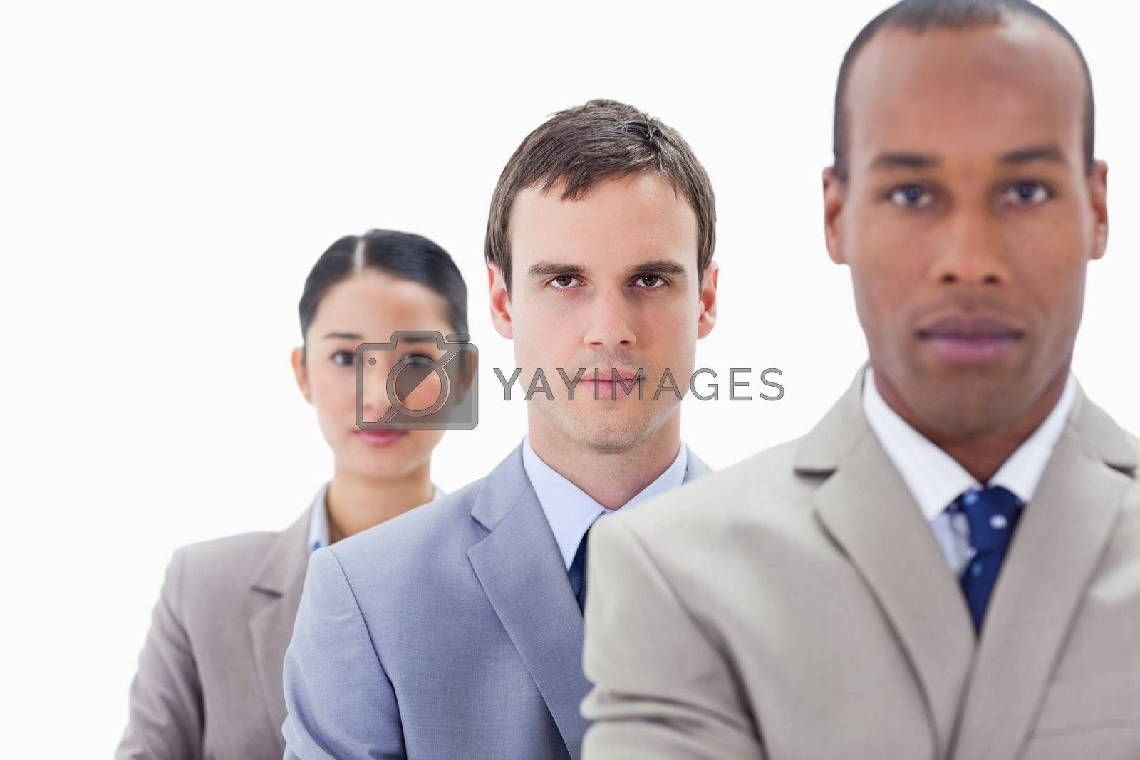 Big close-up of serious workmates in a single line looking straight with focus on the middle man