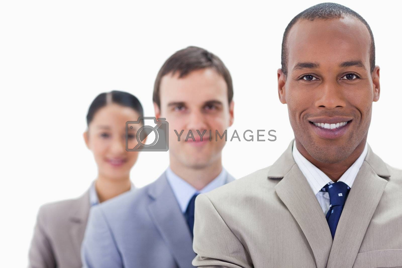 Big close-up of people dressed in suits smiling in a single line with focus on the first man
