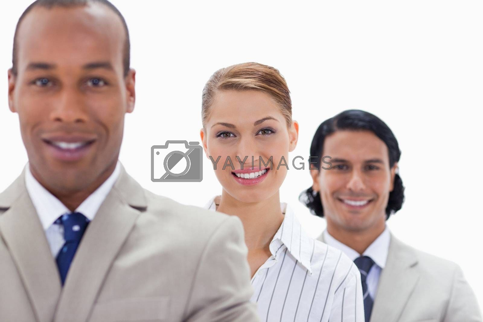 Big close-up of colleagues smiling in a single line with focus on the woman
