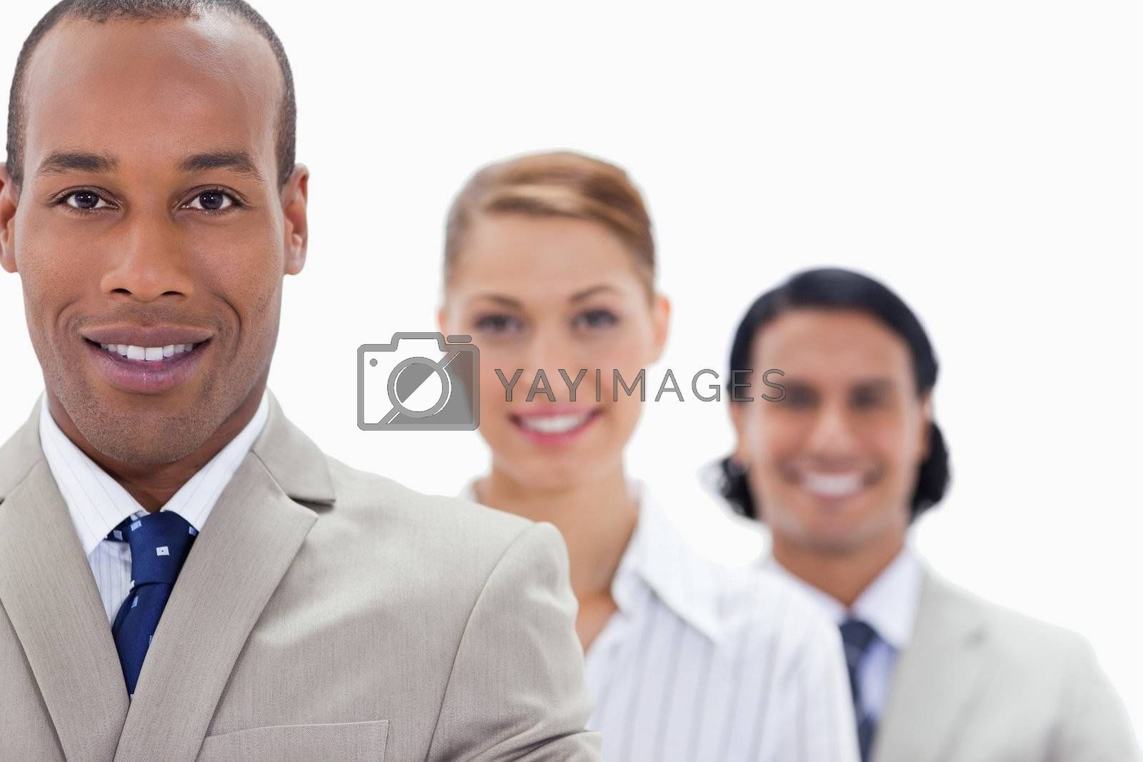 Big close-up of workmates in a single line smiling with focus on the first man