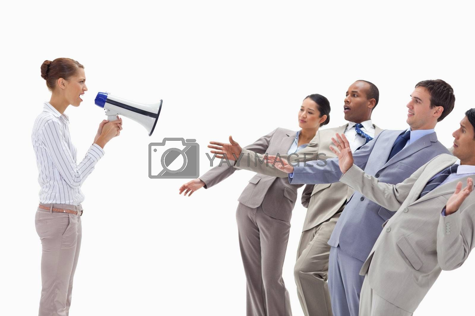 Woman yelling at people dressed in suits through a megaphone against white background
