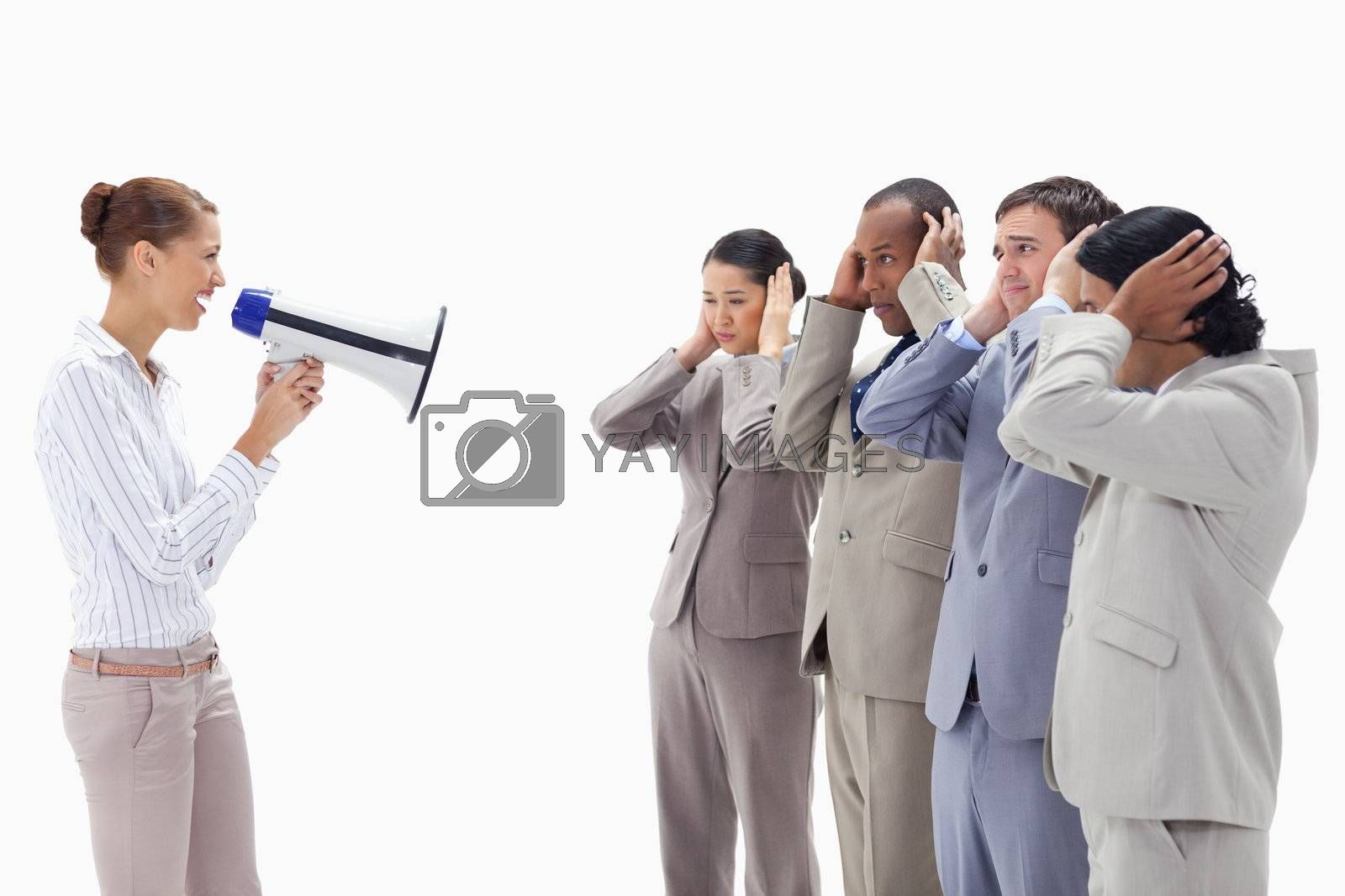 Woman yelling happily through a megaphone at business people with their hands on their ears