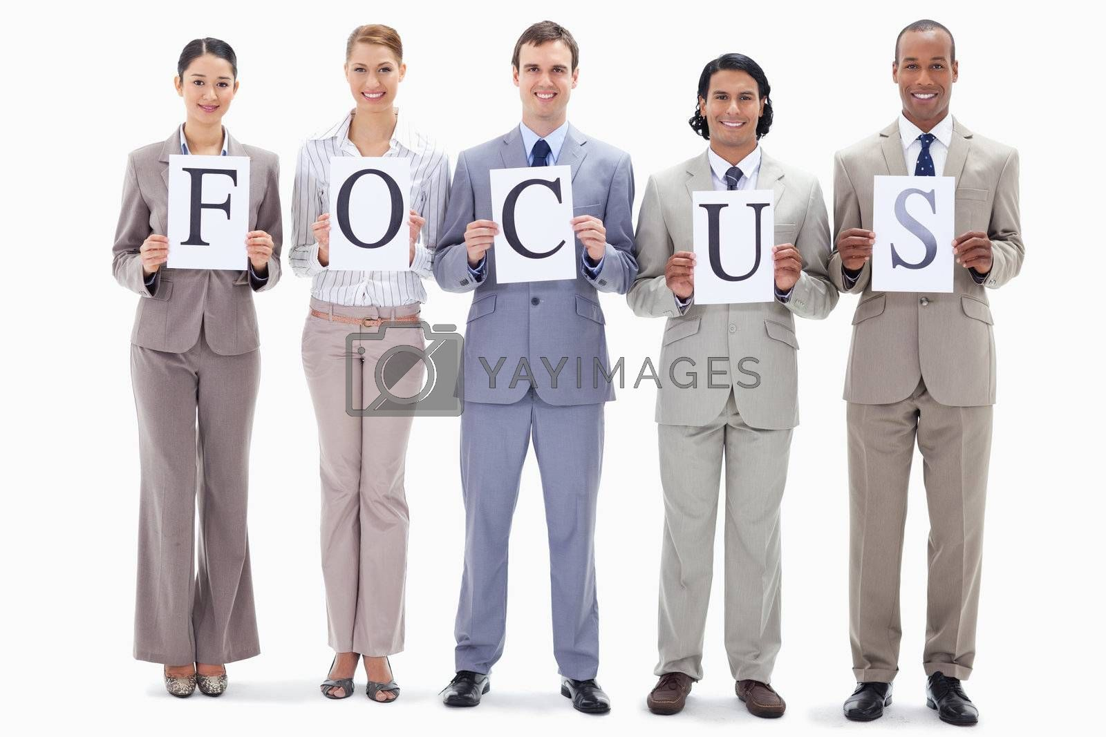 Happy business team holding the letters of FOCUS against white background